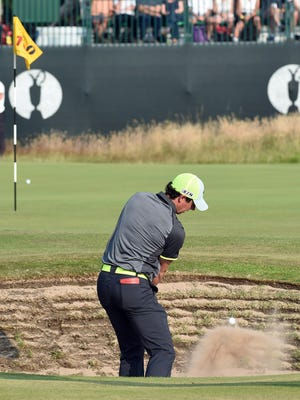 Rory McIlroy hits from a green-side bunker at the 16th hole Friday.