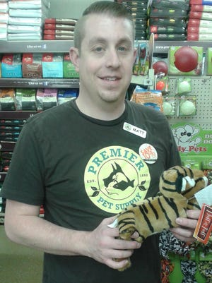Matt Thomason of Canton, assistant manager of Premier Pet Supplies in Beverly Hills, shows a Fluff & Tuff toy for dogs.