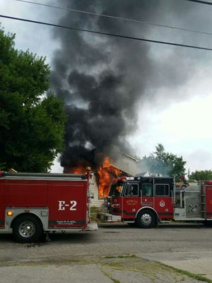 Flames engulf a house on the 1100 block of W. 11th Street around 10 a.m. Wednesday.