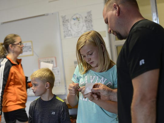 Olivia Kabara, 11, and her father Jeff try to figure out her lock combination during an open house and student orientation Wednesday at Pulaski Community Middle School.