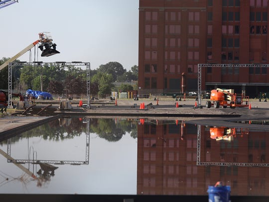 Several cranes with soft boxes and lighting gear are raised over a track in preparation for the filming of a car racing reality show at Eastman Business Park. In the center is water, unknown if it was there on purpose or due to the recent rains.