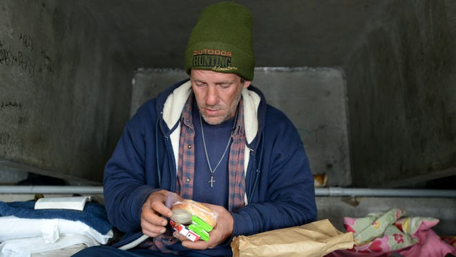 Stosh Szczechowich unpacks a sack lunch, provided by Sean's Outpost homeless outreach program, at his camp under the Pensacola Bay Bridge recently.