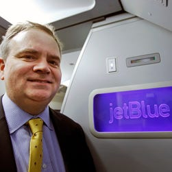 JetBlue' CEO Robin Hayes pauses in front of a JetBlue logo inside an Airbus A321 aircraft at John F. Kennedy airport in New York on Feb. 5, 2015.
