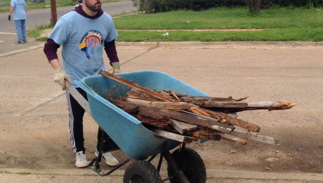 Enterprise Employee moves old wood frames from the garden at Common Ground during United Way's Day of Caring March 18.