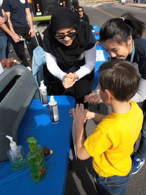 Sara Jahanziria and Nancy Phu, students at Burrell College of Osteopathic Medicine's Foundations in Biomedical Science program, demonstrate proper hand washing technique to a young boy at the downtown Las Cruces farmers and crafts market on a recent Saturday. Thirty-four students in the program put on a health fair at the market.