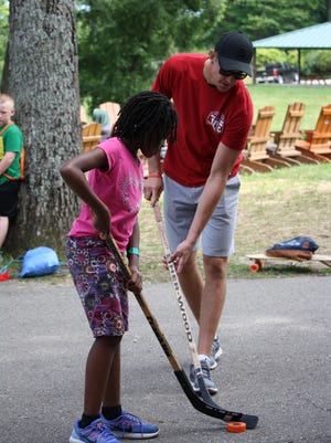 Detroit Red Wings defenseman Danny DeKeyser plays with a camper during a youth hockey event Tuesday, July 27, 2017, at Echo Grove Camp near Oxford.