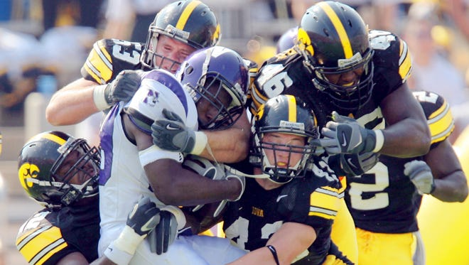 Iowa's Jeremiha Hunter #42, Matt Kroul #53, Pat Angerer #43 and Christian Ballard #46 wrap up Northwestern's Tyrell Sutton #19 on a run attempt in the third quarter of their game at Kinnick Stadium in 2008.