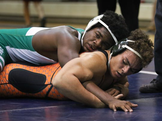 Fort Myers H.S.'s Najee Jacob, top, and Dunbar H.S.'s Judah Bertolloti wrestle for first place in the 195 Weight Class during the LCAC wrestling tournament at Estero High School on Saturday, January 30, 2016.  Najee Jacob won. Photo by Gregg Pachkowski.