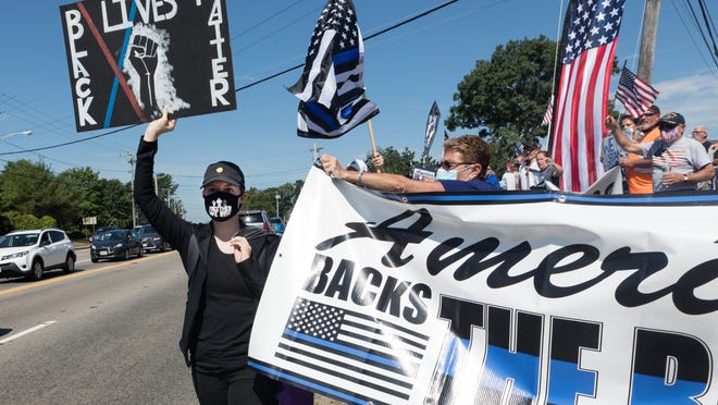 A protester in support of Black Lives Matter holds her sign high as she makes her way to the crosswalk through a crowd of Back The Blue supporters as they try to block her path in Marshfield on Sunday, July 26, 2020.