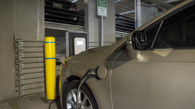 A Ford Fusion Energy is charged at the Blink electric charging station on the third floor of the Baptist Medical Center Parking Garage in Jacksonville Friday. Up to four electric vehicles can charge here at one time.