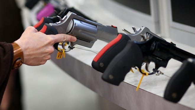 An attendee inspects a handgun during the 2013 NRA Annual Meeting and Exhibits at the George R. Brown Convention Center on May 3, 2013 in Houston, Texas.