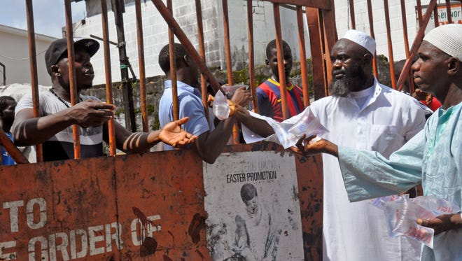 Men working for a humanitarian group give water in small bags to West Point residents behind a gate at a holding area as they wait for a second consignment of food from the Liberian government to be handed out near the central city area of Monrovia on Aug. 22, 2014.