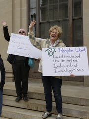 Protesters hold signs and chant outside U.S. Sen. Ron