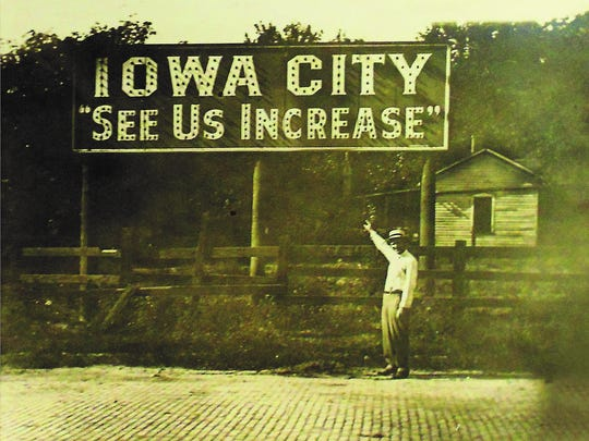 A man poses by an Iowa City sign in the 1920s. It's