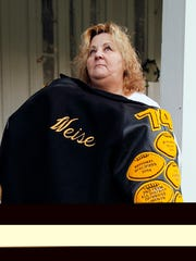 "FILE - In this Nov. 13, 2010 file photo, Arleen Weise, mother of Deepwater Horizon oil rig floorhand Adam Weise, stands on her front porch wrapped in her son's high school football jacket in Yorktown, Texas. Adam Weise was one of 11 workers killed after the Deepwater Horizon exploded in the Gulf of Mexico in April. The film, ""Deepwater Horizon"" is stirring mixed emotions for family members of the 11 men who died in the blast. While their reactions to the movie vary, many relatives share a hope that the film will remind people about the disaster's human toll. (AP Photo/Patrick Semansky, File)"