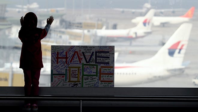 A woman looks at Malaysian planes next to a sign wishing for safe return of passengers aboard the missing Malaysia Airlines Flight 370 plane at Kuala Lumpur International Airport in Sepang, Malaysia.