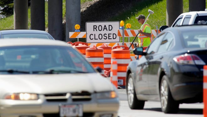 A road construction worker carries a survey tool near the I-43 and Highway 28 construction zone Thursday May 19, 2016 in Sheboygan.  Motorists are urged to take caution in those areas.