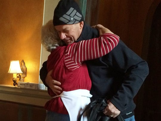 Volunteers' warmth: Emmanuel Tissot, 70, of Jericho, hugs Anna Deller, 80, of South Burlington, after delivering an apple pie Thursday to the free Thanksgiving meal at Sweetwaters American Bistro.