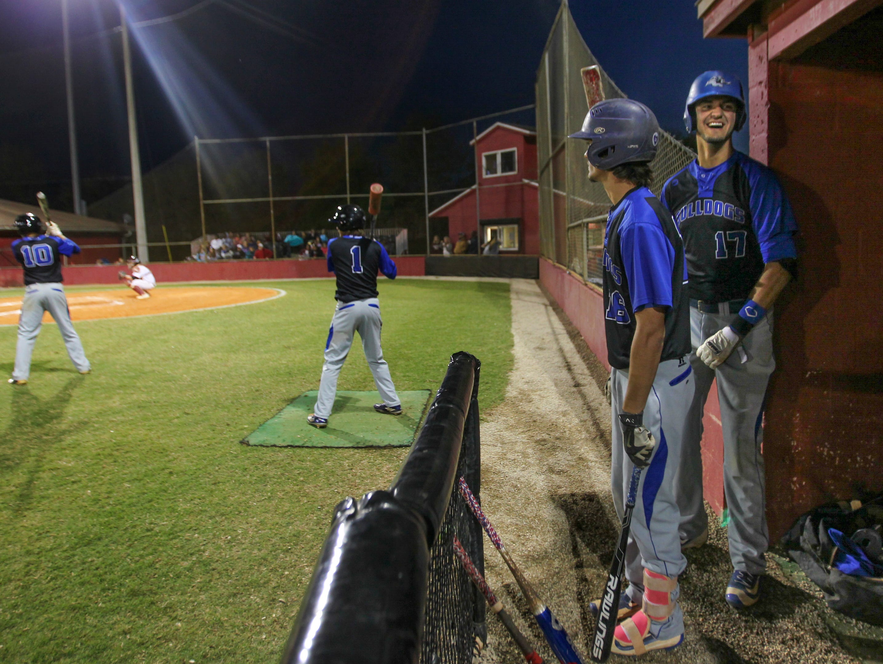 Ida Baker's Christian Menendez, right, laughs while the rest of the team chatters to the opposing team Monday at Riverdale High School in Fort Myers.