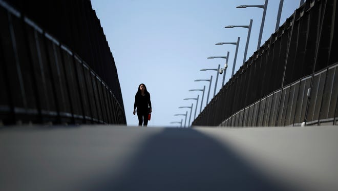 In this Tuesday photo, a woman walks towards the border on a pedestrian bridge over construction on a new curve along California's Interstate 5 as it approaches the border with Tijuana, Mexico. The San Diego-to-Tijuana border crossing, busiest border crossing in the United States, will close this weekend to the more than 40,000 cars that pass through it daily to Mexico.