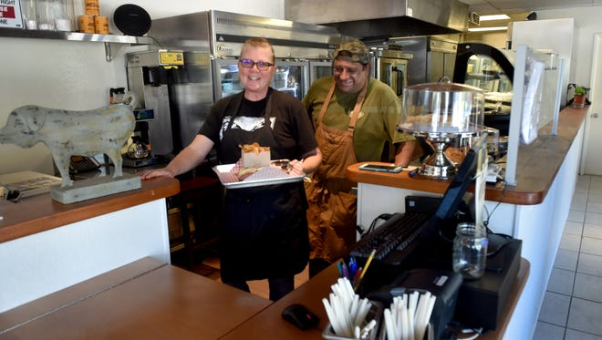 Misty and Ernest Romero, owners of J Wolf Catering and BBQ in Ventura prepare lunch on Monday. The restaurant opened in August at 2271 N. Ventura Avenue.