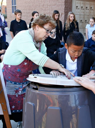 Copper Ridge Elementary school teacher Nanette Hubbell, helps her fifth-grade class secure the lid on a composting container in Scottsdale on Jan. 20, 2016.