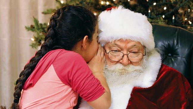 In this file photo, Alejandra Amaya whispers to Santa Claus what she wants for Christmas. Three local chapters of the Beta Sigma Phi sorority have arranged for children to have their pictures taken with St. Nick at the White Sands Mall, with the proceeds going to local charities.