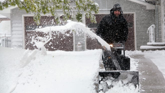 Will Parsons uses a snowblower to clear the driveway of his neighbor on Oak Avenue Sunday morning, May 10, 2015 in Rapid City, S.D. Some parts of Rapid City saw 10 inches of snow by Sunday morning with more forecast throughout the day. (Chris Huber/Rapid City Journal via AP) TV OUT