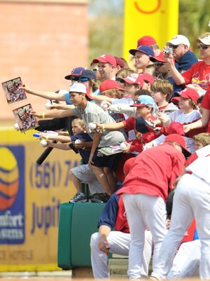 Baseball fans at Roger Dean Stadium clamor for autographs from the players.