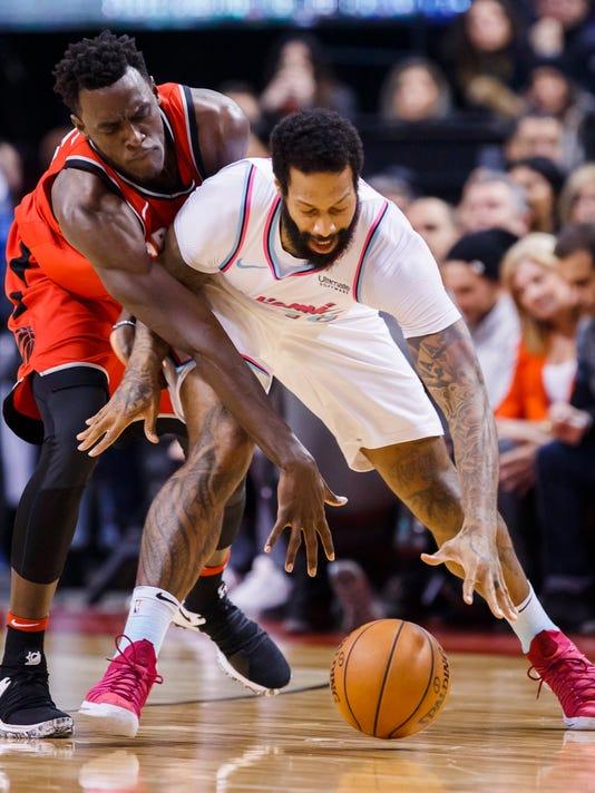 Toronto Raptors' forward Pascal Siakam reaches around Miami Heat forward James Johnson, right, during the first half of an NBA basketball game, Tuesday, Feb. 13, 2018, in Toronto. (Mark Blinch/The Canadian Press via AP)