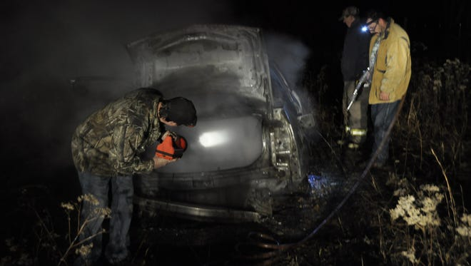 Oakland Promise Land Volunteer firefighters check a burned Cadillac for victims Tuesday night after finding the car fully enguled in flames. Fire chief Lucy Soltysik called the fire suspicious.