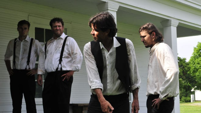 Film director Darrin James, middle right, directs actors Jake Rotger, Joseph Calhoun and Joe Rogala, left to right, on the porch of a Brighton home featured in his independent horror film Elder Island.