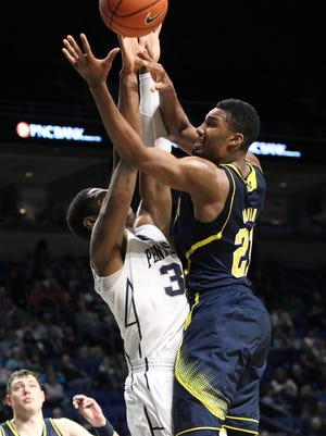 Michigan's Zak Irvin drives the ball to the basket as Penn State's Jordan Dickerson guards during the second half Tuesday at Bryce Jordan Center. Michigan defeated Penn State 73-64.