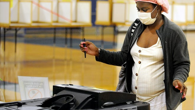 At the Framingham Keefe Technical School voting place, Courtney Williams casts her ballot on Tuesday, Nov. 3, 2020.