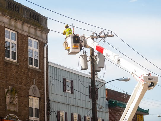 A utilitary worker checks electric lines at 109 E.