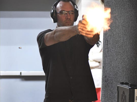 Ian MacDonald of Grand Blanc fires a pistol during a class as he seeks to get a concealed pistol permit license.