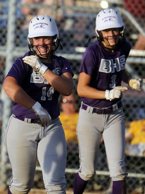 Burlington High School's Kayla Norton (14) and Carley McGinity (3) smile as they head back to the dugout after scoring during their Class 4A regional quarterfinal against Mount Pleasant High School, Thursday July 16, 2020 at Burlington's Wagner field.