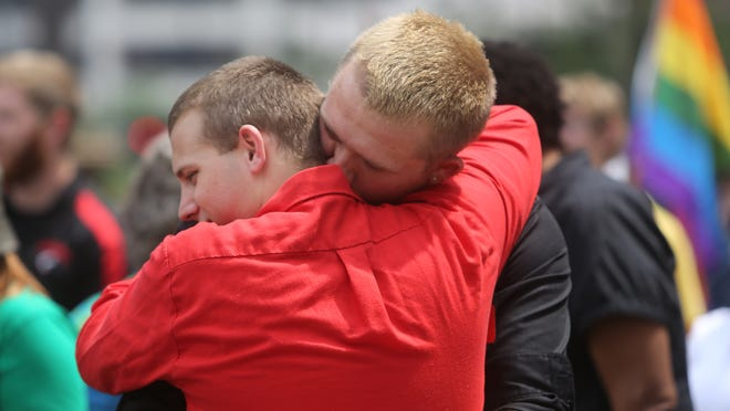 Tyler Darby, left, and Ryan Gambrell hug each other on Wednesday, August 6, 2014. Lawyers from four states ready to argue before an appellate panel weighing whether same-sex marriage bans are unconstitutional at the local Federal Courthouse. There was a rally for Marriage Equality on Fountain Square. Meanwhile, people in favor of the gay marriage bans prayed outside the Federal Courthouse.