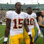 Washington Redskins wide receiver Josh Morgan (15) and quarterback Robert Griffin III (10) walk off the field following the game against the Green Bay Packers at Lambeau Field.