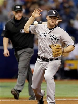 New York Yankees third baseman Chase Headley makes an error on a ground ball by Tampa Bay Rays' Mikie Mahtook during the sixth inning of a baseball game Monday, Sept. 14, 2015, in St. Petersburg, Fla.  (AP Photo/Chris O'Meara)