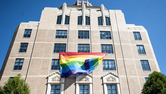 A large rainbow flag hangs from the fourth floor of
