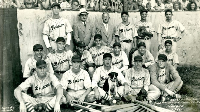 Championship 1940 Beacon Blanketeer team, photo by J.C. Wolcott. Front row, from left: Melton Ellis, Bassie Moore, Harley Fox, Smokie the mascot, Henry Burrell and Rex Bryant; second row: Carl Poteat, Bill Horne, Wayne Martin, Mark Ferguson, Ray Nichols, Woodrow Patton and Wade Martin; back row: Bill Barnwell, A.G. Magent, superintendent, Jack Share, plant manager, Quentin Martin, Charles Talent and Bill Rhymer.