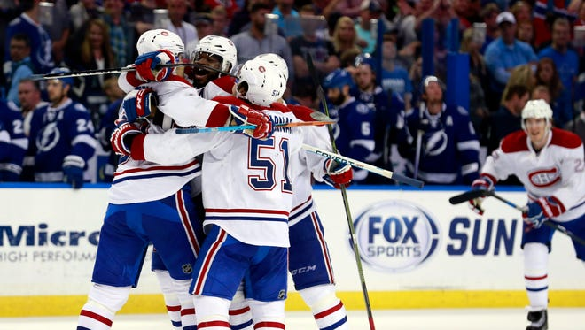 Montreal Canadiens left wing Max Pacioretty (67) is congratulated by defenseman P.K. Subban (76) and teammates as he scores the game winning goal during a shootout against the Tampa Bay Lightning at Amalie Arena.