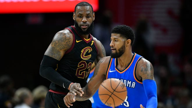 Cleveland Cavaliers forward LeBron James (23) defends Oklahoma City Thunder forward Paul George (13) in the third quarter at Quicken Loans Arena.