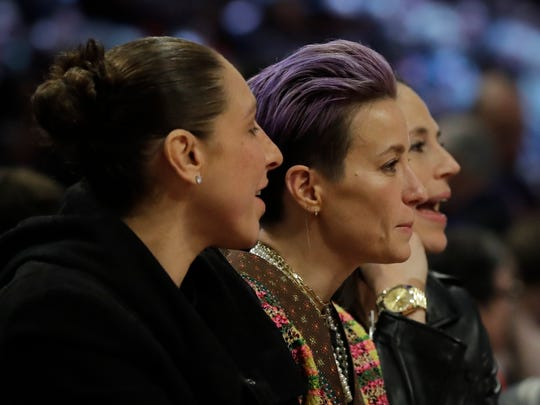 Basketball player Diana Taurasi, soccer player Megan Rapinoe and basketball player Sue Bird, from left, are seen during the second half of the NBA All-Star basketball game Sunday, Feb. 16, 2020, in Chicago. (AP Photo/Nam Huh)