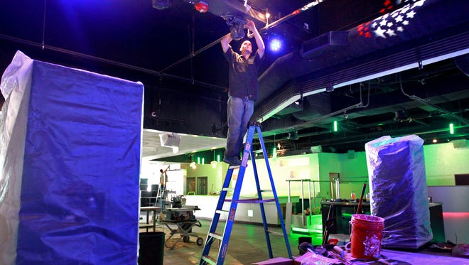 Erik Hawley, with Advanced Audio Video, works on the extensive LED light system at the new downtown entertainment venue Xtra 920 on July 24, 2014, in Appleton, Wis.  Wm.Glasheen/Post-Crescent Media