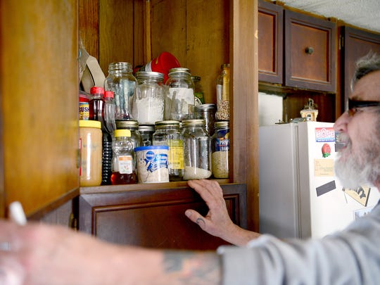 David Cooke shows off his pantry in his home in rural Madison County. He must keep his food in sealed jars to keep bugs out.