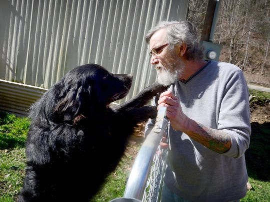David Cooke plays with one of his dogs behind his home in Madison County. Cooke has three dogs he keeps in the home and fenced-in area behind it.