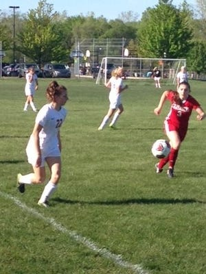 Plymouth Christian's Allie Crecelius (22) chips the ball toward the Lutheran Northwest goal during Thursday's game.
