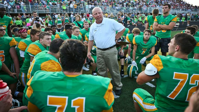 Floyd Central football coach Brian Glesing motivates his team during a break in the action against Providence. The coach has Hodgkin's Lymphoma and didn't coach in the first game.